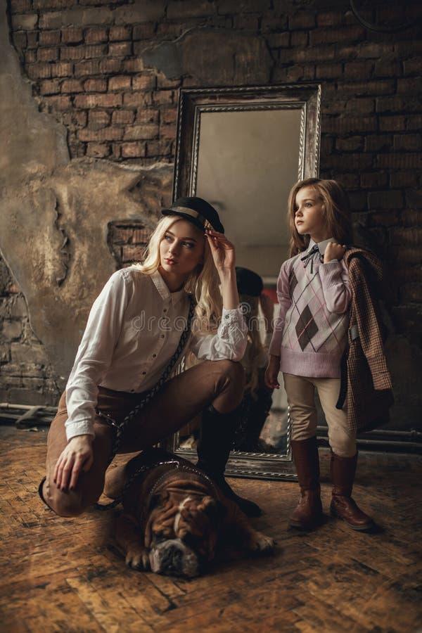 La fille d'enfant avec la femme dans l'image de Sherlock Holmes se tient à côté du bouledogue anglais sur le fond du miroir et du photo stock