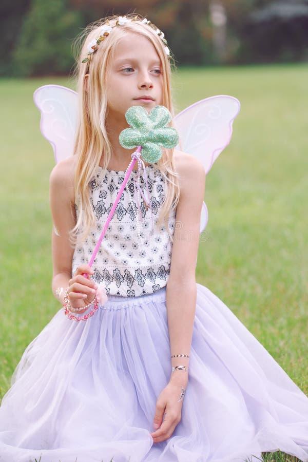 La fille d'enfant d'enfant avec de longs cheveux utilisant les ailes féeriques roses et le tutu Tulle bordent tenir la baguette m image stock