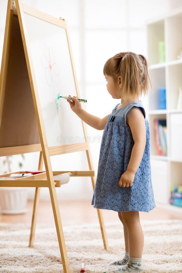 La fille d'enfant dessine sur un conseil blanc avec un stylo feutre images stock