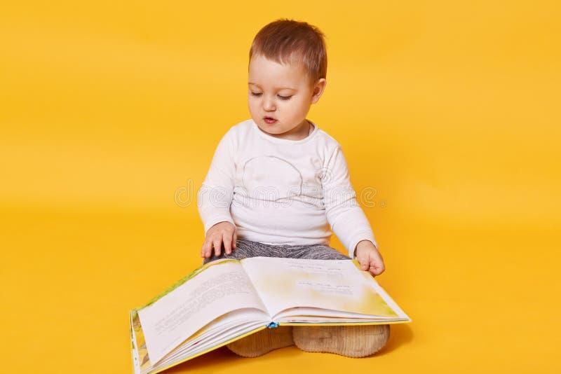 La fille d'enfant en bas âge feint pour lire le livre tout en se reposant sur le plancher, les images de visionnement et les page photos stock