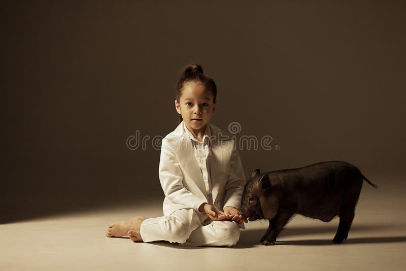 La fille d'enfant est reposante et alimentante le porcelet vietnamien noir photographie stock libre de droits