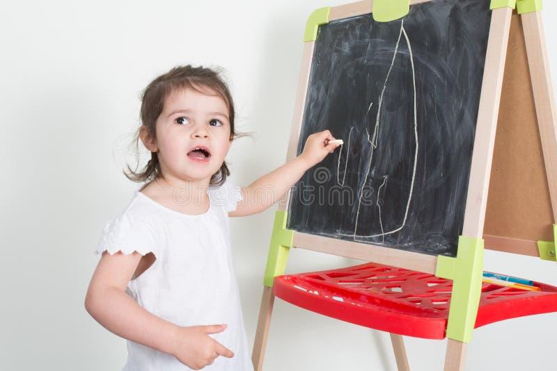 La fille d'enfant fait des dessins de craie sur un tableau photo libre de droits
