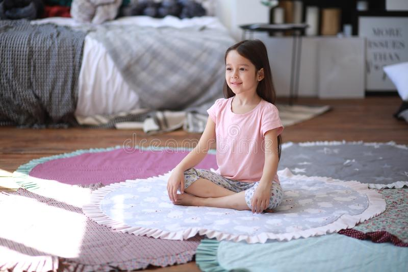 La fille d'enfant fait des exercices de yoga sur le tapis images libres de droits