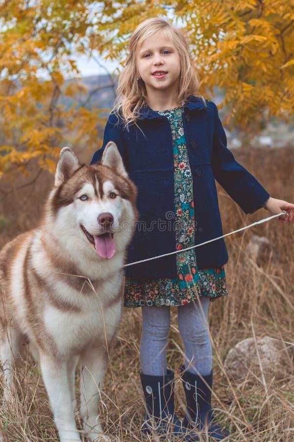 La Fille D'enfant Marche Avec Le Chien Enroué Mignon Photo