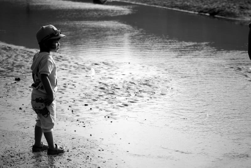 La fille d'enfant prennent un coucher du soleil de mer d'alerte d'étape images libres de droits