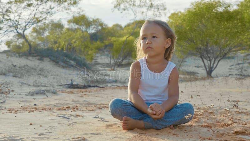 La fille d'enfant s'assied au désert et somethink de considérer avec le regard fixe de mille-yard image libre de droits