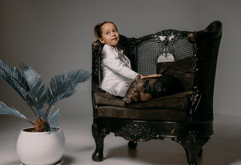 La fille d'enfant s'assied dans le fauteuil avec le porcelet vietnamien à côté de photos stock
