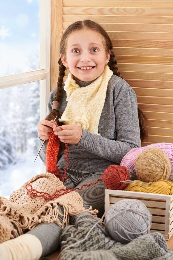 La fille d'enfant s'assied sur un filon-couche de fenêtre avec des fils et le tricotage de laine Belle vue en dehors de la fenêtr image stock