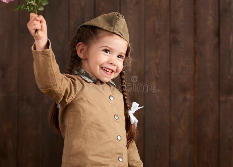 La fille d'enfant sont habillées comme soldat dans de rétros uniformes militaires photo stock