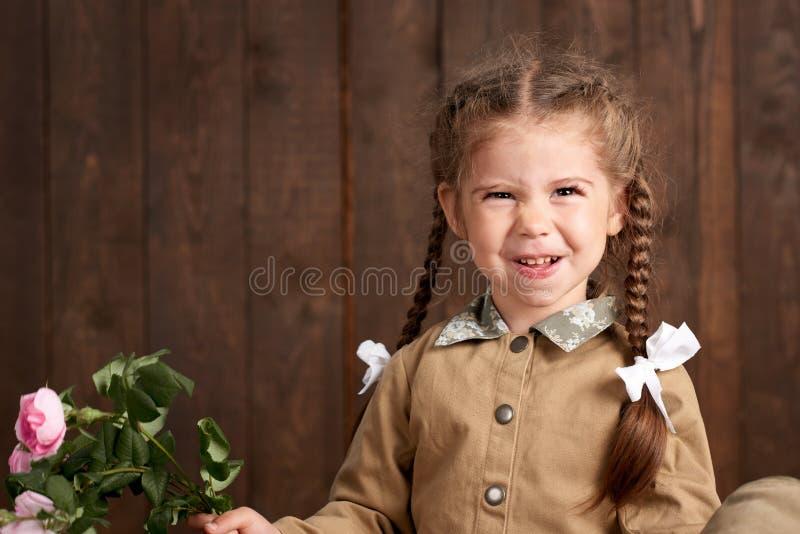 La fille d'enfant sont habillées comme soldat dans de rétros uniformes militaires images libres de droits