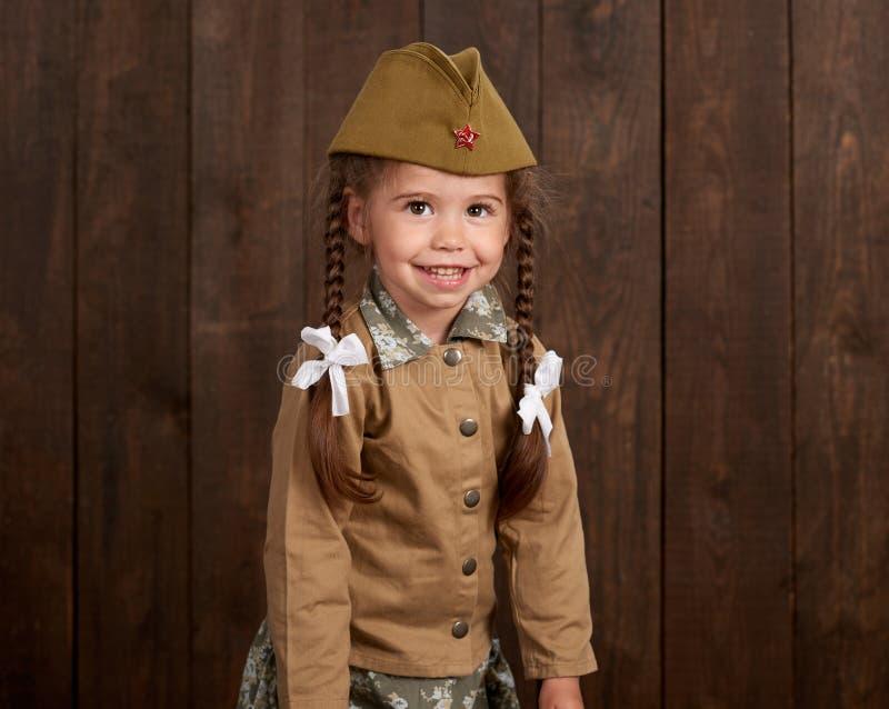 La fille d'enfant sont habillées comme soldat dans de rétros uniformes militaires photographie stock libre de droits