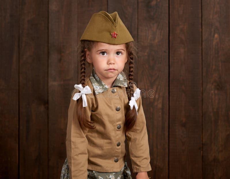La fille d'enfant sont habillées comme soldat dans de rétros uniformes militaires images stock
