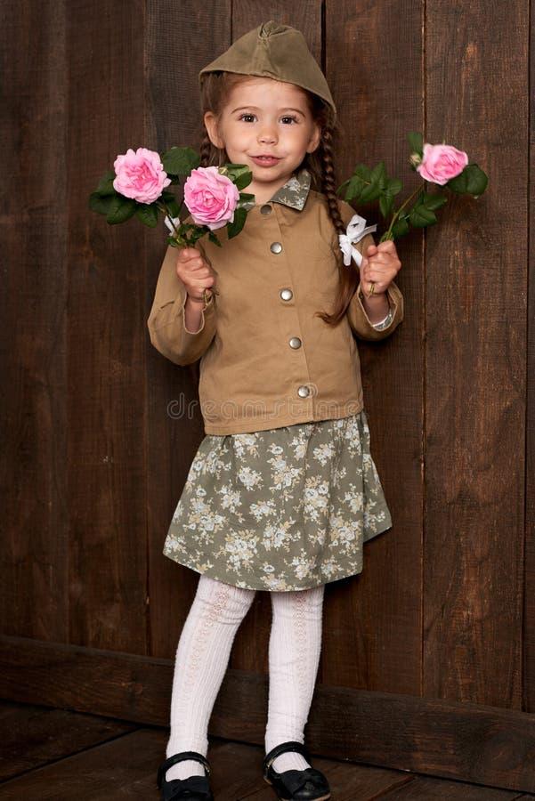 La fille d'enfant sont habillées comme soldat dans de rétros uniformes militaires photos libres de droits