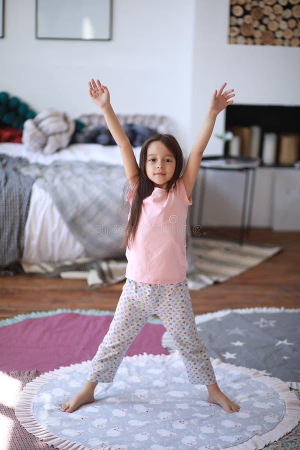 La fille d'enfant tient et fait des exercices de matin photos libres de droits
