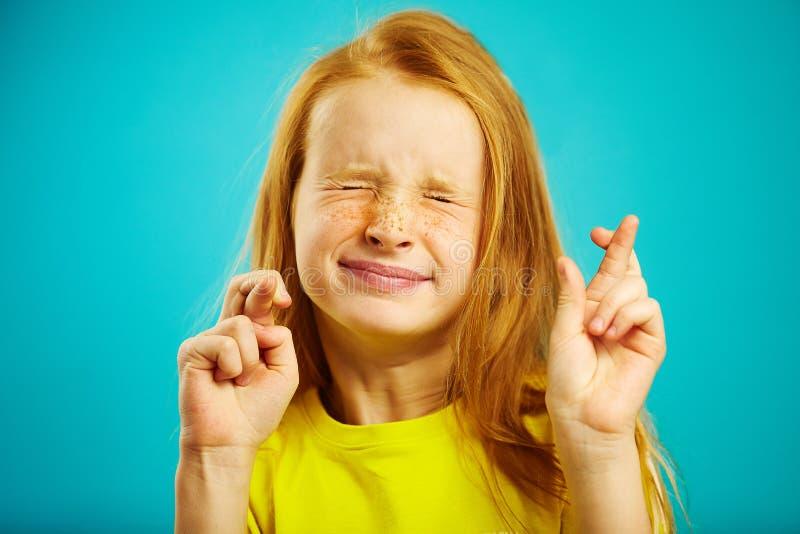 La fille d'enfants a étroitement fermé ses yeux et les doigts mis croisés, font un souhait, croient en rêve, exprime sincère photo libre de droits