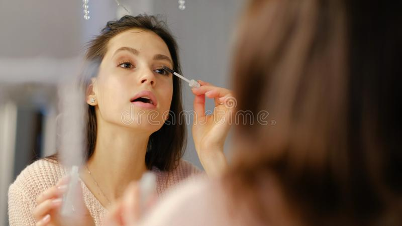 La fille d'instruction de blog de maquillage de beauté appliquent le mascara photographie stock