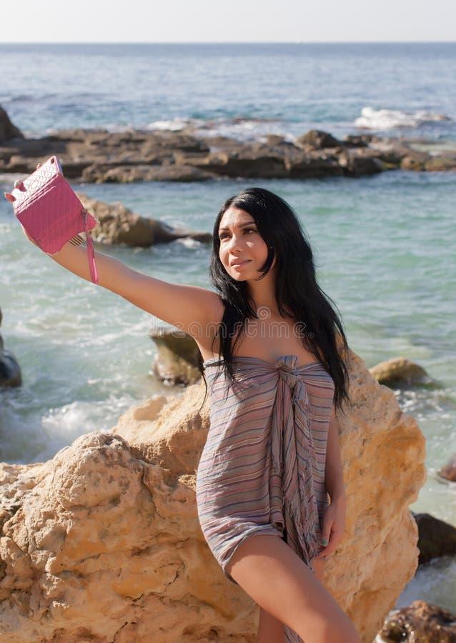 La fille d'une chevelure foncée dans des sarongs fait le selfie contre la mer photographie stock libre de droits