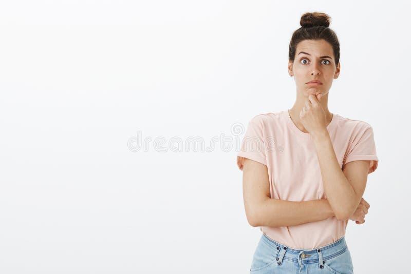 La fille dans d'idées étranges de écoute de stupeur d'ami, incertaines comment le dire est menton stupide et pinçant et lèvres so photographie stock