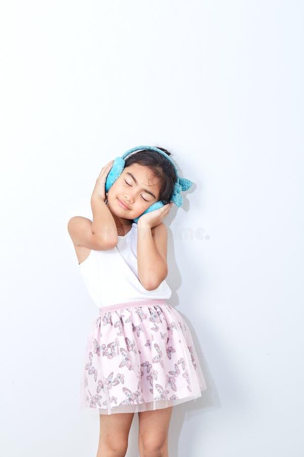 la fille dans des bouche-oreilles d'hiver sourient heureux photos libres de droits