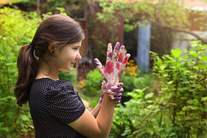 La fille dans des gants de robe et de jardin de point de polka l'été verdissent le fond de pays images libres de droits
