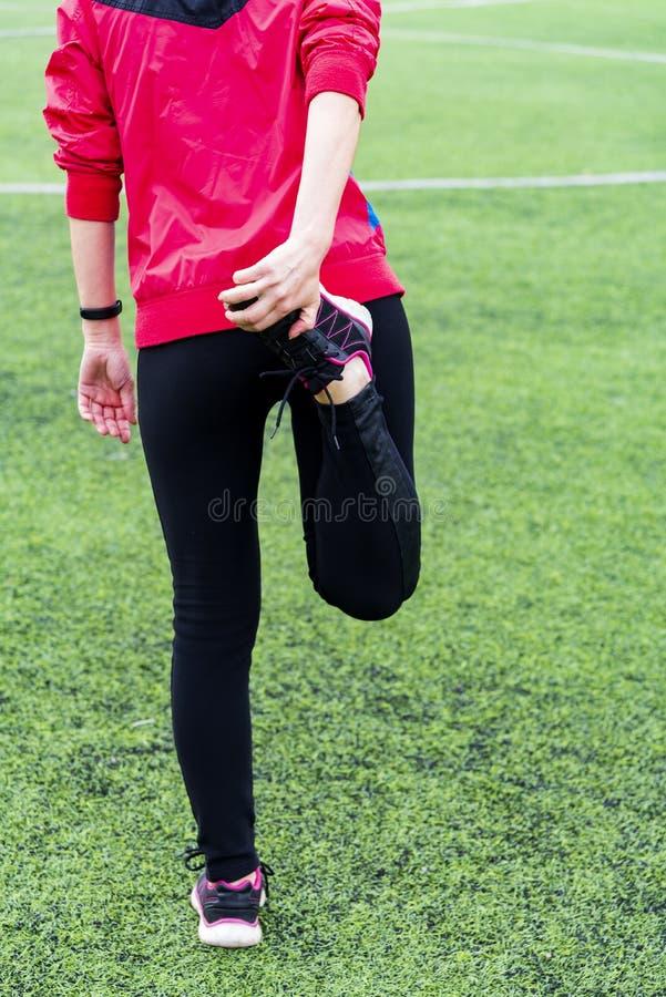 La fille dans des guêtres noires de sports et une veste rose malaxe avant la formation dans une arène de sports ouverte photos libres de droits