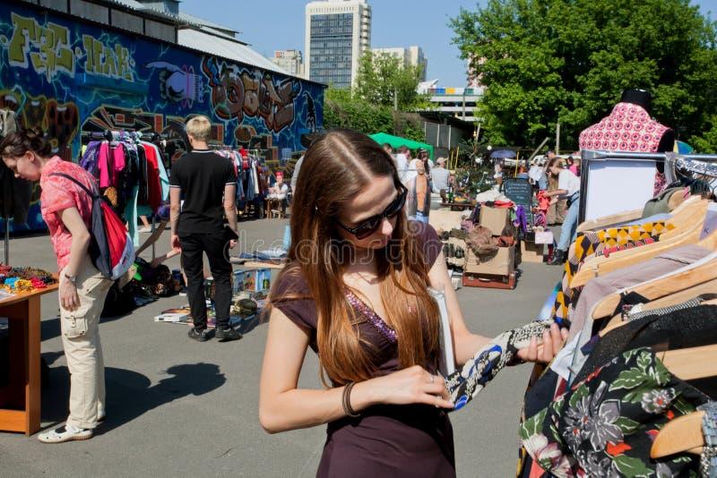 La fille dans des lunettes de soleil choisit la chemise sur le marché aux puces de rue photos libres de droits
