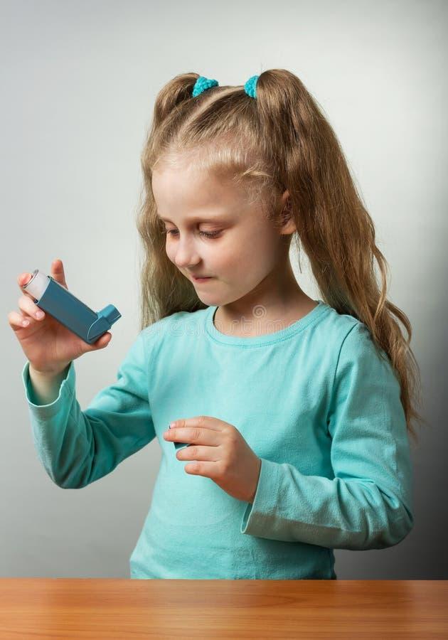 La fille dans des prises d'un chemisier de turquoise mettent en boîte de la médecine contre l'asthme sur le fond gris photo stock