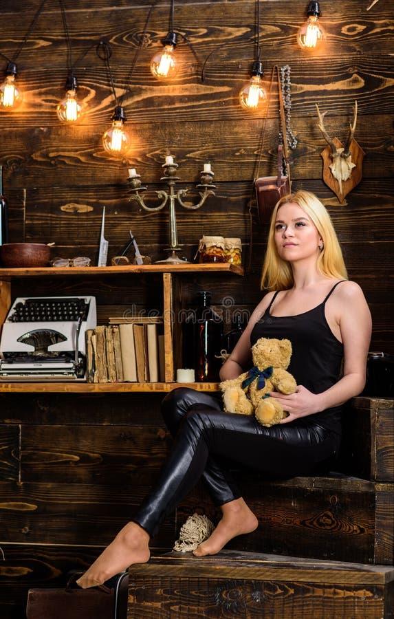 La fille dans des vêtements noirs juge le jouet d'ours de nounours intérieur disponible et en bois sur le fond Femme sur le visag images libres de droits