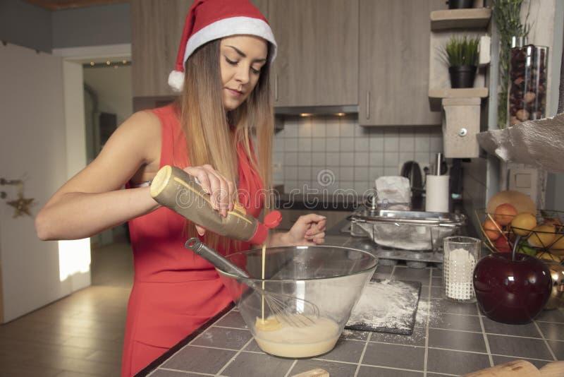 La fille dans l'habillement de Noël, dispose à faire un gâteau, ajoute des ingrédients image libre de droits