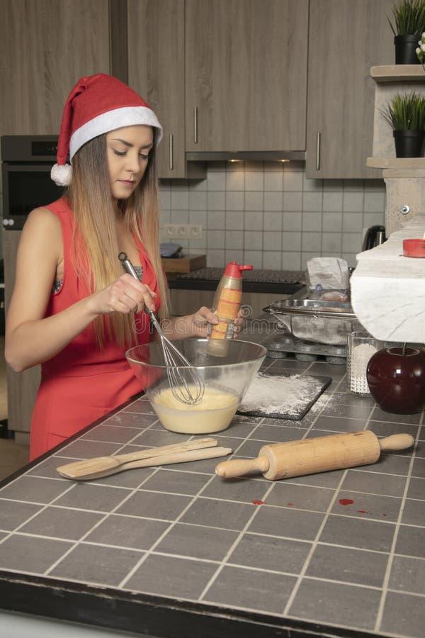 La fille dans l'habillement de Noël, dispose à faire un gâteau, vue de côté photo libre de droits