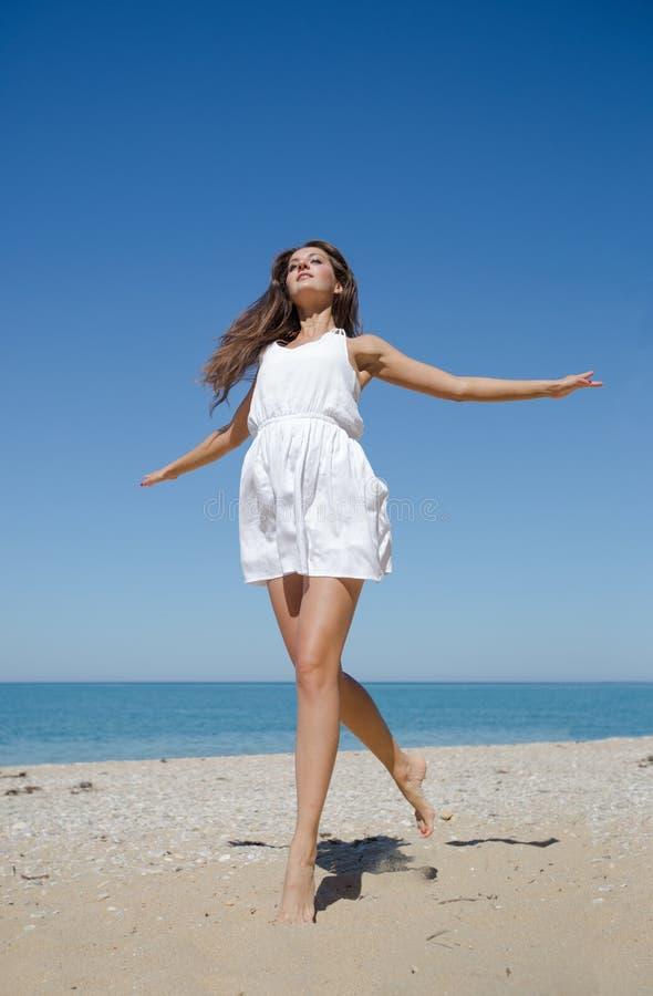 La fille dans la robe blanche saute sur le bord de la mer de sable image stock