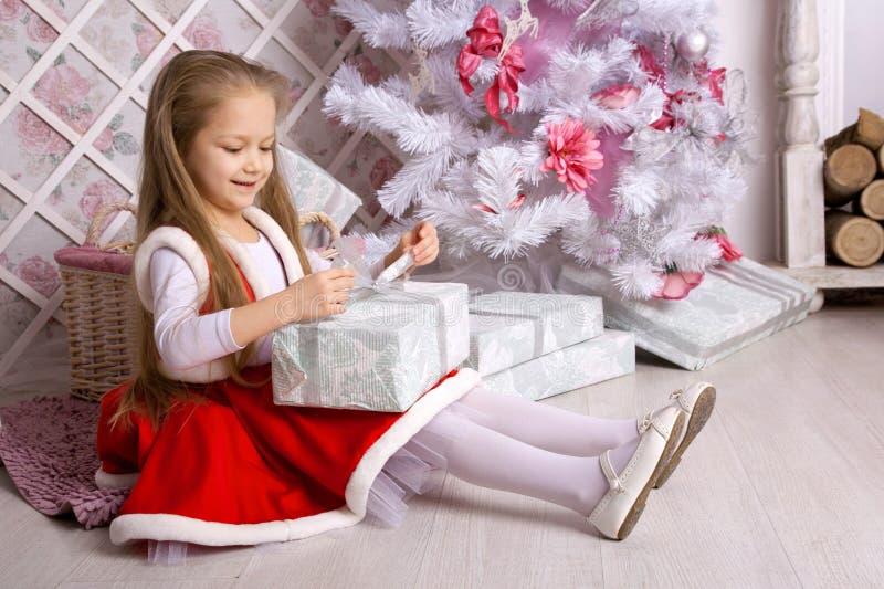 La fille dans la robe de Noël ouvre des présents photographie stock