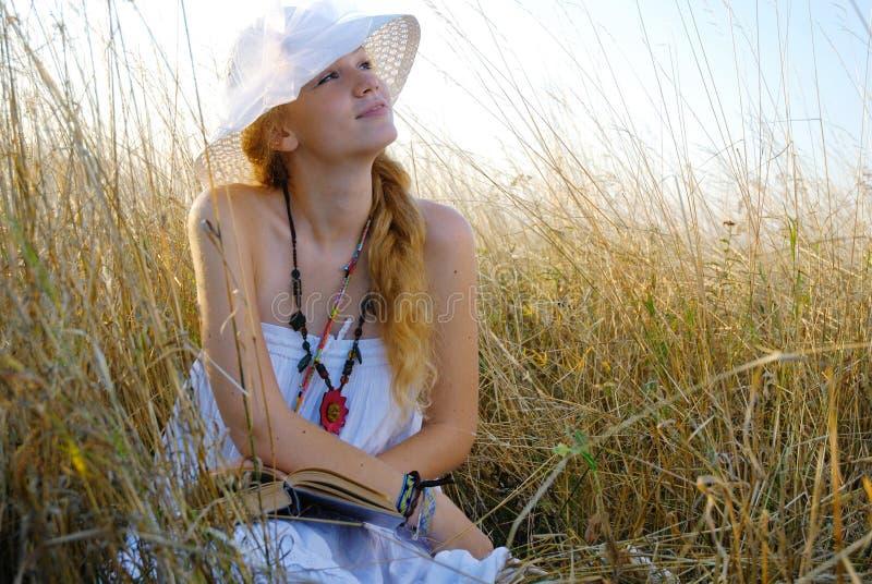 La fille dans la séance et la lecture de chapeau un livre images stock