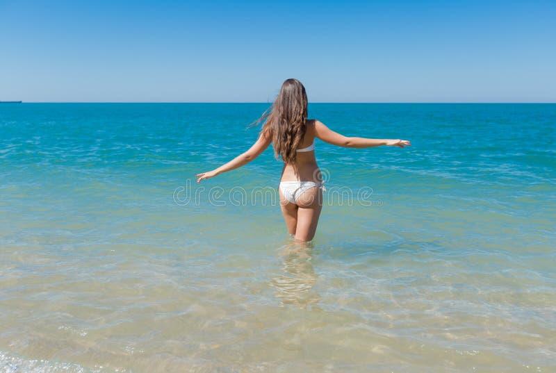 La fille dans le bikini blanc entre dans la mer photo libre de droits