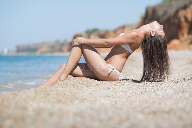 La fille dans le bikini blanc repose le penchement de retour photo stock