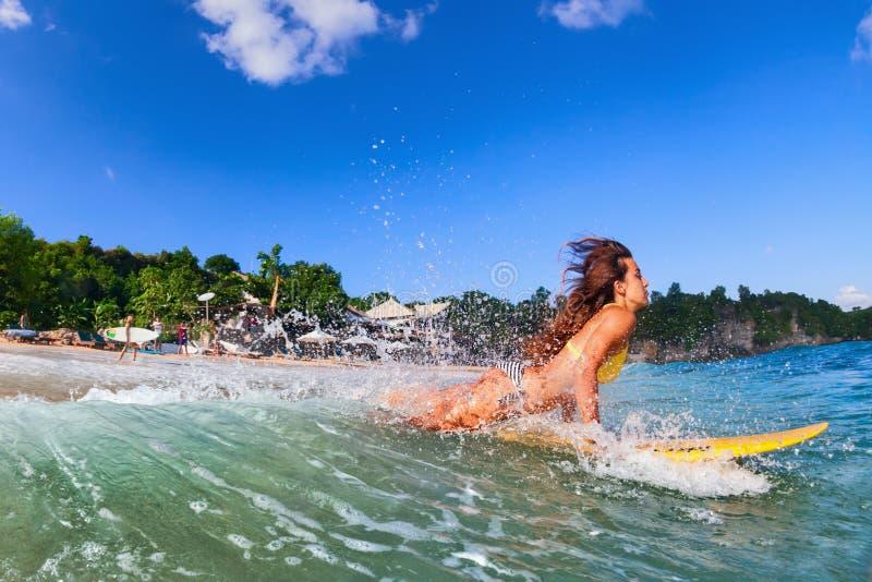 La fille dans le bikini a un amusement sur le panneau de ressac images stock