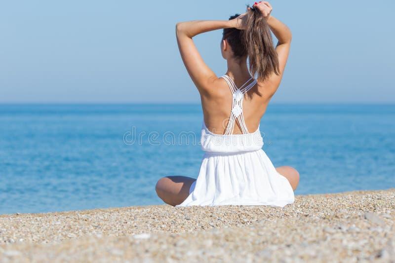 La fille dans le blanc s'assied sur le bord de la mer de caillou corrigeant la coiffure photographie stock