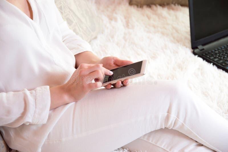 La fille dans le blanc tient le téléphone dans des ses mains Lisez les nouvelles au téléphone Un homme avec un téléphone dans des photographie stock