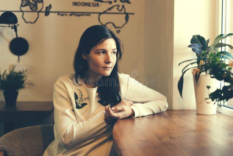 La fille dans le café par la fenêtre photo stock