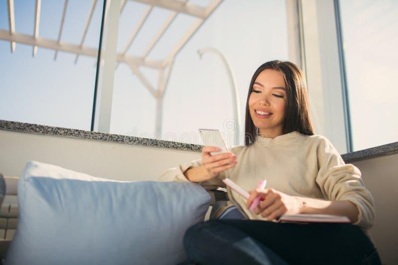 La fille dans le chandail blanc s'assied sur le sofa et regarde au téléphone Elle tient un carnet dans sa main et sourire photos libres de droits