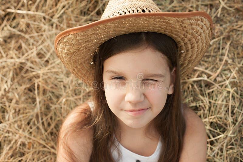La fille dans le chapeau avec un a fermé l'oeil image stock