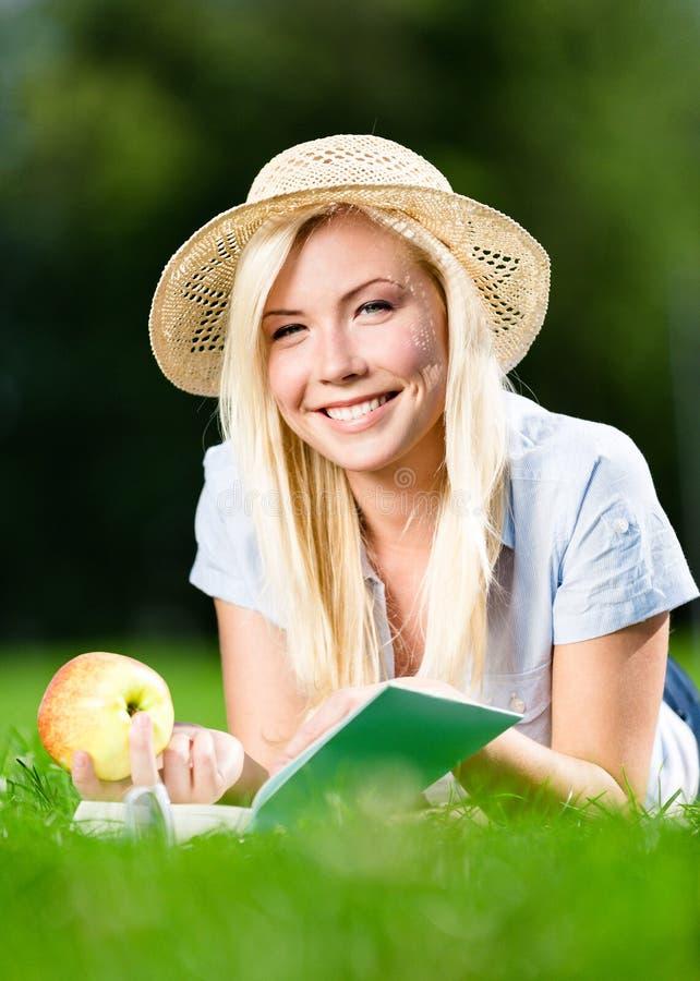 La fille dans le chapeau de paille avec la pomme lit le livre sur l'herbe photo libre de droits