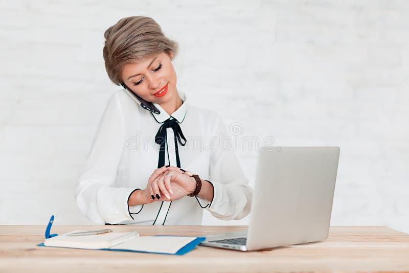 La fille dans le chemisier blanc s'assied à la table avec l'ordinateur portable et regarde l'horloge image stock