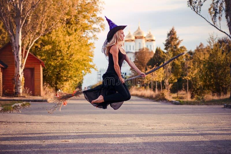La fille dans le costume de Halloween vole sur un manche à balai images libres de droits