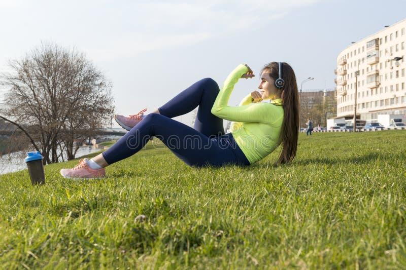 La fille dans le dessus vert de sports occupé dans les fintess sur la pelouse dans la ville dehors, fille secoue la presse photos stock