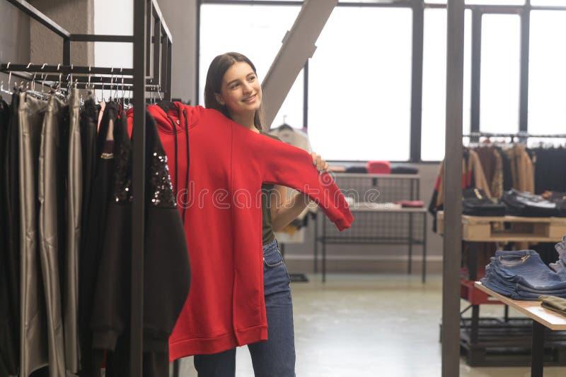 La fille dans le magasin choisit ses nouvelles choses, un pull molletonné rouge photos stock