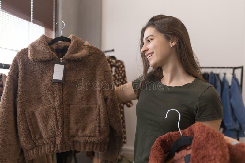 La fille dans le magasin d'habillement choisit entre deux manteaux de fourrure photos stock