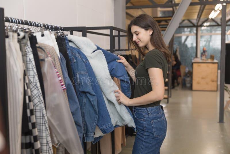 La fille dans le magasin d'habillement choisit la veste de denim photographie stock