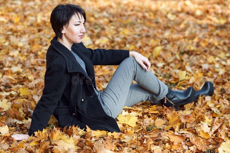 La fille dans le manteau noir se reposant sur un jaune part, saison d'automne, parc de ville, image libre de droits