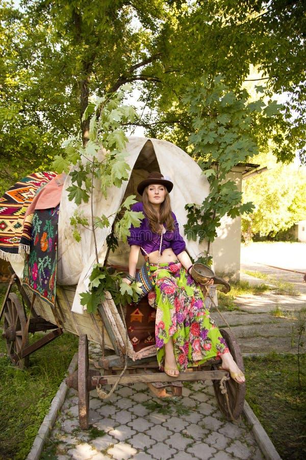 La fille dans le style de Bohème dans un chariot gitan dans le chapeau photos stock